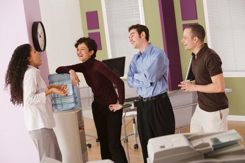 Businesspeople chatting by water cooler